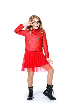 Cute ten year old girl posing in studio in red leather jacket, skirt and boots. Isolated over white. Beauty, fashion.