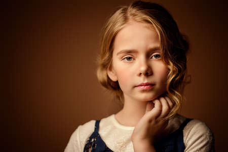 Portrait of a beautiful eight year old girl with calm pensive look. Childhood concept.  Stock Photo