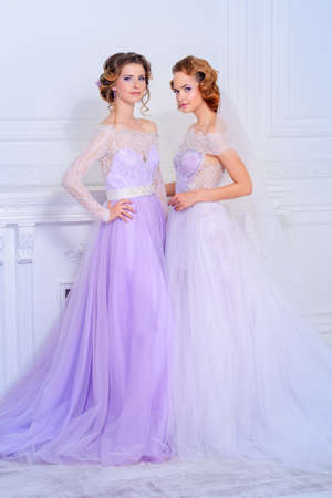 Charming bride and bridesmaid stand together in beautiful dresses and smile. Wedding fashion.
