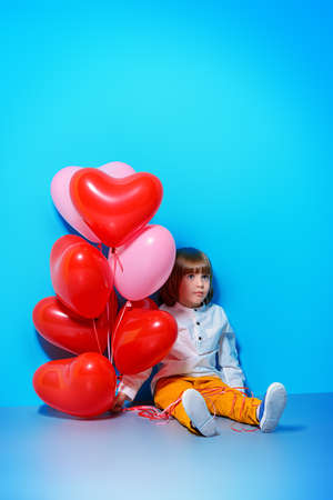 ?ute six-year-old boy holding heart shaped balloons over blue background. Valentines Day.