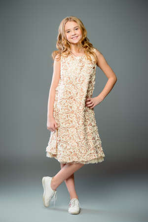 Children's fashion. Cute nine year old girl with long blonde hair posing in summer dress. Studio shot. Full length portrait.