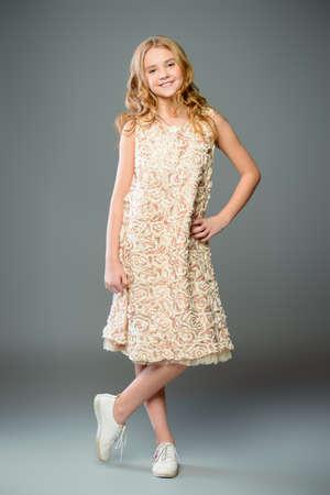 Children's fashion. Cute nine year old girl with long blonde hair posing in summer dress. Studio shot. Full length portrait.