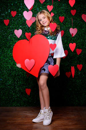 Full length portrait of a pre-teen girl holding red heart surrounded by hearts over lawny background. First love. Valentine's Day. Banco de Imagens