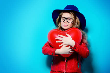 Pretty ten-year-old girl holding heart shaped balloon over blue background. First love. Valentine's Day. Imagens - 95381856