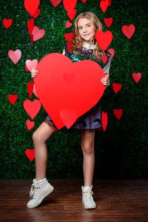 Ganzaufnahme von Posen eines jugendlichen Mädchens umgeben durch Herzen über lawny Hintergrund. Erste Liebe. Valentinstag.