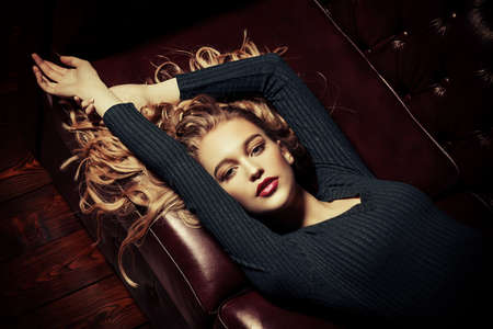 Attractive young woman lies on a leather sofa in a tight black dress. Beauty, fashion. Evening makeup and hairstyle.