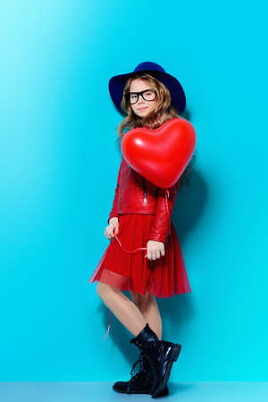 Full length portrait of a pretty pre-teen girl holding heart shaped balloon over blue background. First love. Valentines Day.