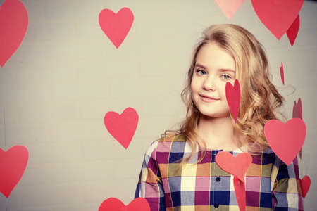 Valentine's Day concept. Happy pre-teen girl poses surrounded by little hearts. First love. Imagens - 95383671