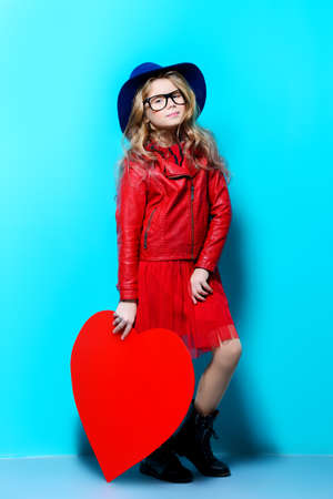 Full length portrait of a pretty pre-teen girl holding big red heart over blue background. First love. Valentines Day.  Imagens
