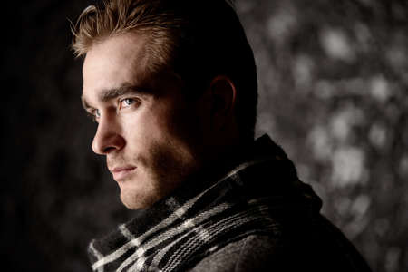 Male beauty, fashion. Portrait of a handsome man wearing coat and scarf. Seasonal clothes collection. Stock Photo - 95537654