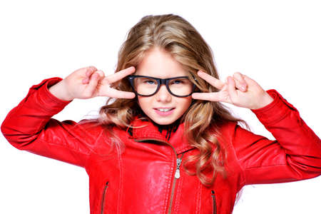 Portrait of a cool ten year old girl posing in studio in red leather jacket. Isolated over white. Beauty, fashion. 写真素材