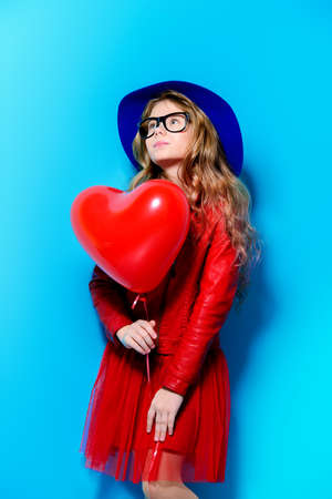 Pretty ten-year-old girl holding heart shaped balloon over blue background. First love. Valentines Day.