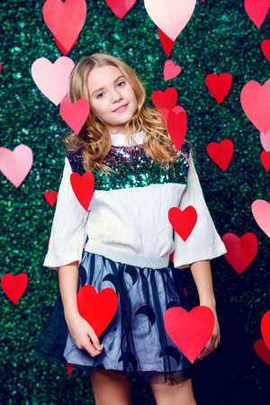 Happy pre-teen girl pose entouré de petits coeurs sur fond de pelouse. Premier amour. La Saint-Valentin.