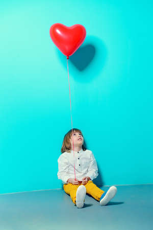 Сute six-year-old boy holding heart shaped balloon over blue background. Valentines Day.