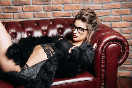Seductive girl in the black lingerie and  fur jacket lying on a leather sofa. Luxurious lifestyle. Fashion, beauty. Studio shot. Standard-Bild