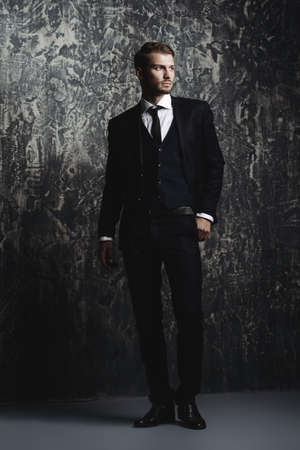 Full length portrait of a handsome man in an elegant suit on a grunge background. Studio shot. Stock Photo