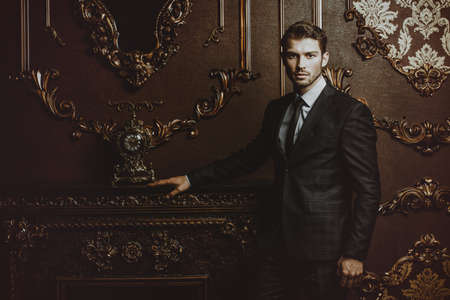 Imposing well dressed man in a luxurious apartments with classic interior. Luxury. Mens beauty, fashion. Фото со стока