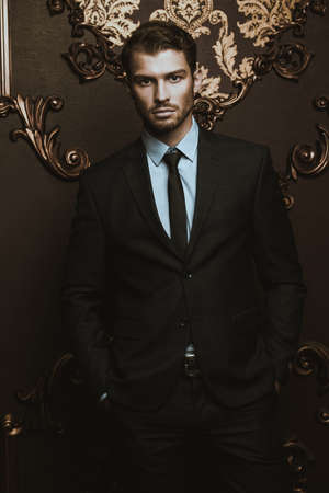 Imposing well dressed man in a luxurious apartments with classic interior. Luxury. Mens beauty, fashion. Stock fotó