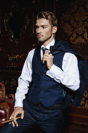 Imposing well dressed man in a luxurious apartments with classic interior. Luxury. Mens beauty, fashion. Stock Photo
