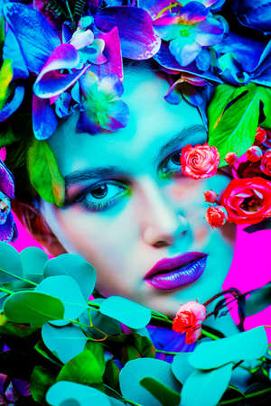 Beauty portrait. Beautiful brunette woman with sensual lilac lips surrounded by flowers. Spring look. Cosmetics, make-up. Perfumery. Foto de archivo