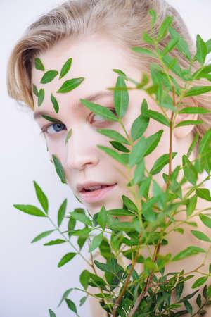 Schöne junge Frau mit grünen Blättern auf ihrem Gesicht über weißem Hintergrund . Kosmetik und Make-up