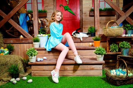 イースターの休日。幸せな女の子は、木造住宅の近くのポーチにニンジンでウサギを養っています。田舎のスタイル、イースターの装飾。