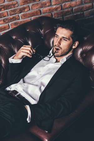 Portrait of a sexy handsome man on a leather sofa. Luxurious lifestyle. Fashion shot. Mens clothing and accessories. Stock Photo
