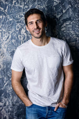 Portrait of a handsome smiling young man wearing white t-shirt. Studio shot over dark background. Men's beauty and health.