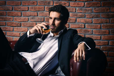 Portrait of a sexy handsome man drinking wine on a leather sofa. Luxurious lifestyle. Fashion shot. Mens clothing and accessories.