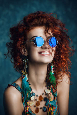 Close-up portrait of a beautiful bright woman with curly foxy hair in sunglasses, earrings and beads. Ethnic style in accessories. Stockfoto