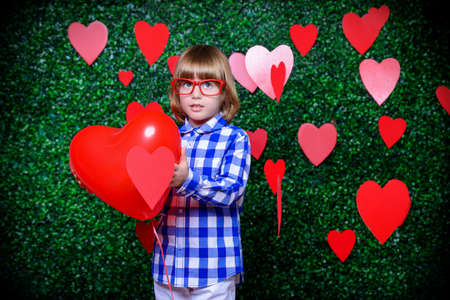 �¡ute child boy holding heart shaped balloon, surrounded by hearts over lawny background. First love. Valentines Day.