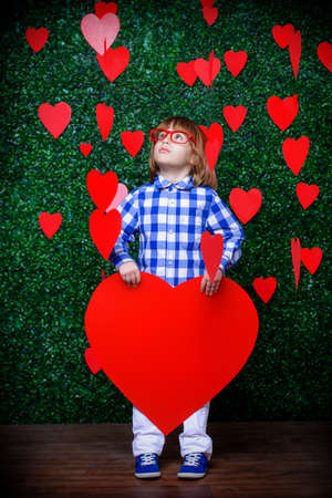 �¡ute child boy holding big heart surrounded by little hearts over lawny background. First love. Valentines Day.