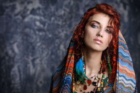 Close-up portrait of a beautiful red-haired woman wears a kerchief and earrings in boho style. Ethnic style in accessories.