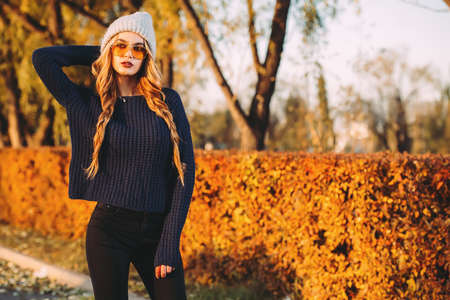 Modern young woman wearing warm clothes posing in the autumn park.