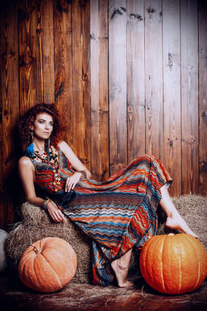 Beautiful bright woman with curly foxy hair sits on a haystack. Stockfoto