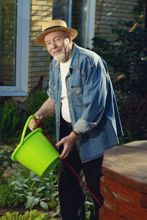 Portrait of a happy senior man standing in his garden on a sunny summer day. Stock Photo - 96461321