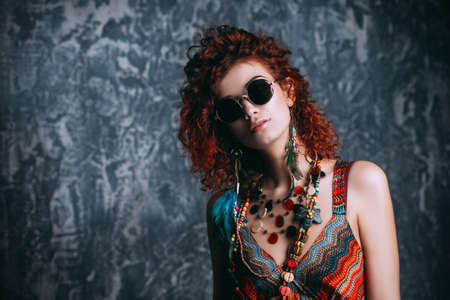 Close-up portrait of a beautiful bright woman with curly foxy hair in sunglasses, earrings and beads. Stockfoto