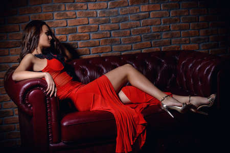 Gorgeous attractive woman in a beautiful red dress is sitting on a leather couch in a luxury apartment.