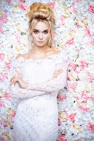 Close-up portrait of a beautiful bride woman posing by background of roses. Archivio Fotografico