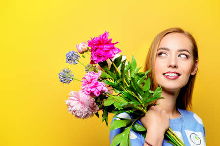Portrait of a beautiful smiling young woman with a bouquet of summer flowers over bright yellow background. Floral Perfume. Beauty, cosmetics. Copy space.
