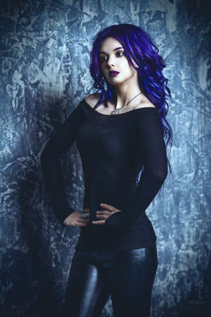 Attractive young woman with purple hair dressed in a black sweatshirt and leather pants. Beauty, youth fashion. Hair coloring. Cosmetics, make-up.