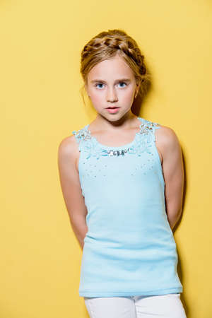 Bright summer girl. Cute eight-year-old girl in summer clothes posing over yellow background. Stock Photo