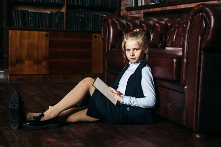 Cute schoolgirl sitting near the couch and reading book. School fashion. Educational concept.