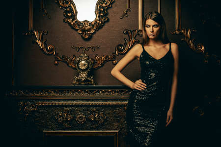 Portrait of an attractive young woman in tight black dress in a luxury apartment. Classic vintage interior. Beauty, fashion. Stok Fotoğraf