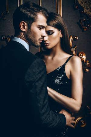 エレガントなイブニングドレスで性的情熱的なカップル。豪華なインテリア。ファッションショット。