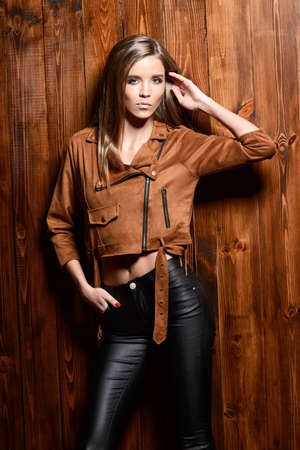 Pretty young woman in a brown jacket and leather trousers posing by a wooden wall. Youth style, fashion.