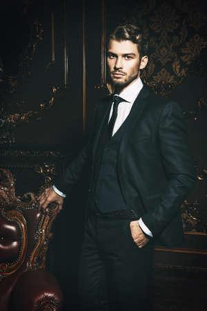 Imponente hombre bien vestido en un lujoso apartamento con interior clásico. Lujo. Belleza masculina, moda. Foto de archivo