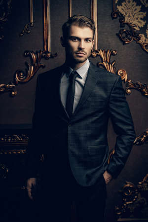 Imposing well dressed man in a luxurious apartments with classic interior. Luxury. Mens beauty, fashion. Banco de Imagens