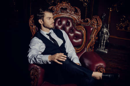 Imposing well dressed man  sitting in an armchair in a luxurious apartments with classic interior. Luxury. Mens beauty, fashion. Stock Photo