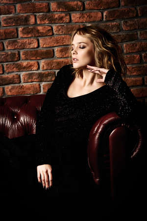 Attractive young woman posing on a leather sofa in a black dress. Beauty, fashion. Evening makeup and hairstyle. Banque d'images - 96779406